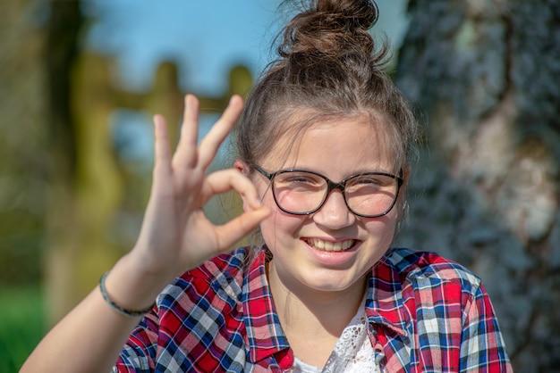 Young teenage girl making ok sign