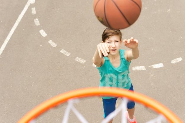 彼女のバスケットボールを練習している若い10代の少女