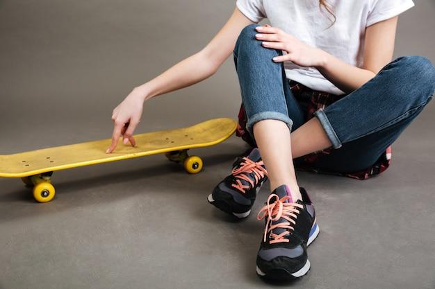 Giovane ragazza seduta sul pavimento con skateboard