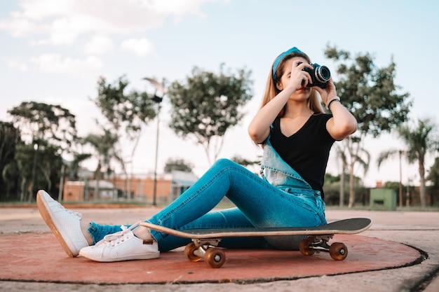 Молодая девочка-подросток, сидя на скейтборде, на открытом воздухе фотографирует с помощью камеры.