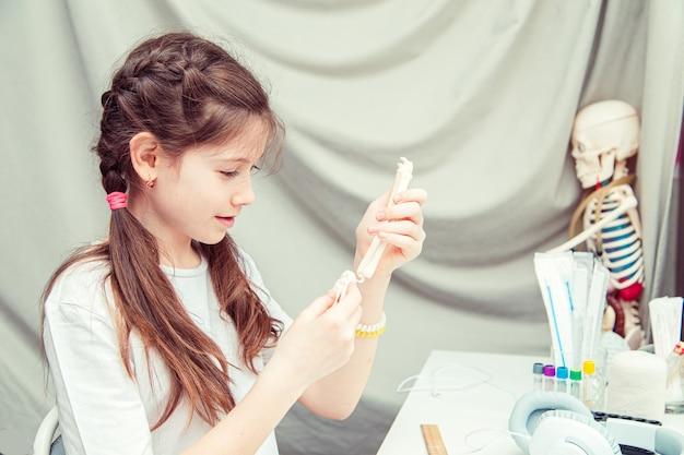 집에서 인체 해부학을 공부하는 어린 10대 소녀. 그녀는 팔의 뼈를 측정합니다. 특이한 취미.