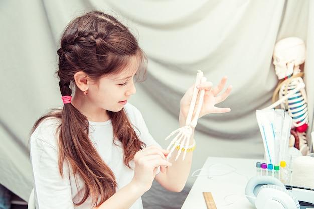 집에서 인체 해부학을 공부하는 젊은 십 대 소녀. 그녀는 팔의 뼈를 측정합니다. 특이한 취미.