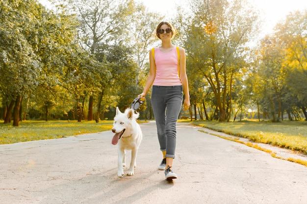 Молодая девушка гуляет с белой собакой хаски на дороге