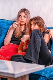 Молодая девочка-подросток смотрит телевизор со своей матерью, когда они обнимаются на диване, перекусывая попкорном в большой ванне в тускло освещенной комнате