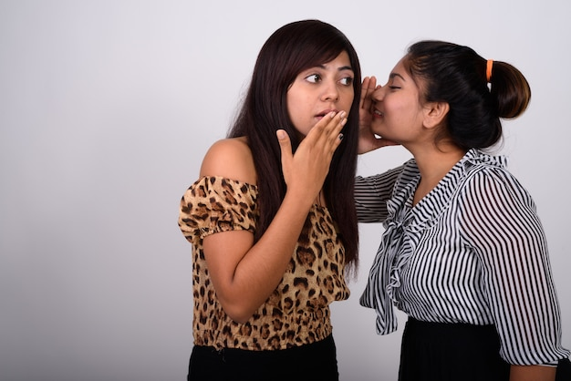 Young teenage girl whispering to young woman thinking while looking shocked
