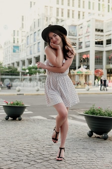 Young teenage girl in a white dress and hat. style of the big city. sunset sky and rays of the sun. natural beauty pretty woman in black fedora hipster hat, on warm summer evening sunset in big city
