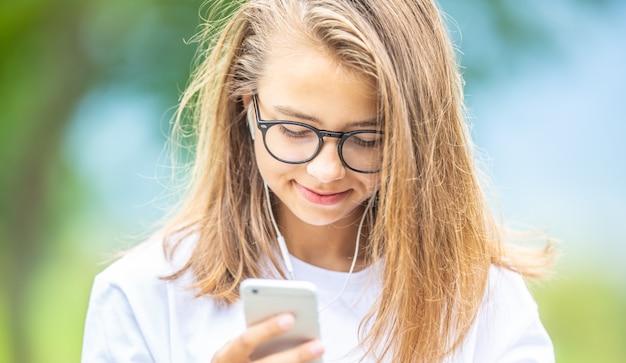 良い音楽を楽しんでいるヘッドフォンを持つ若い10代の少女。携帯電話を持つ現代の若い女性。