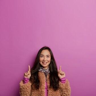 Giovane adolescente con lunghi capelli lisci punta il dito indice sullo spazio della copia, pubblicizza l'oggetto sul muro bianco verso l'alto, vestito con un cappotto invernale