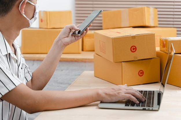 Young teenage man as freelance working with laptop computer and packing of postal parcel box in living room at home