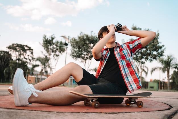 Молодой человек-подросток, сидя на скейтборде, на открытом воздухе фотографирует с помощью камеры.