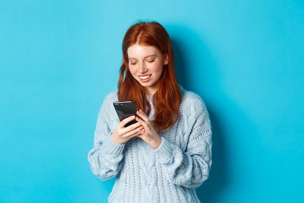 젊은 십 대 빨간 머리 소녀 스마트 폰에서 메시지를 읽고 웃 고, 휴대 전화를 사용 하 고 파란색 배경 위에 서.