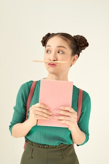 Young teenage student freaking out and holding her pencil between nose and lips as moustache looking funny and naughty