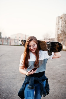 Young teenage urban girl with skateboard, wear on glasses, cap and ripped jeans at the yard sports ground on sunset making selfie on phone.