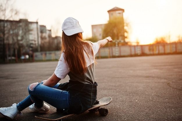 Young teenage urban girl with skateboard, wear on glasses, cap and ripped jeans at the yard sports ground on sunset showed finger on sky.