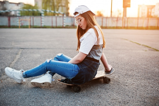 Young teenage urban girl with skateboard, wear on glasses, cap and ripped jeans at the yard sports ground on sunset.
