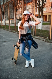 Young teenage urban girl with skateboard, wear on glasses, cap and ripped jeans at the yard sports ground.