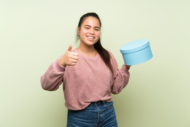 Young teenager asian girl holding gift box