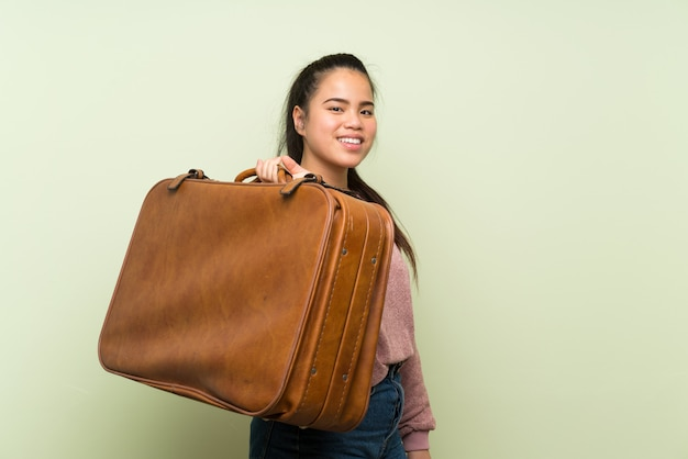 Young teenager asian girl over isolated green wall holding a vintage briefcase