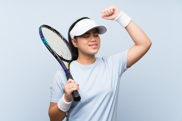 Young teenager asian girl playing tennis celebrating a victory