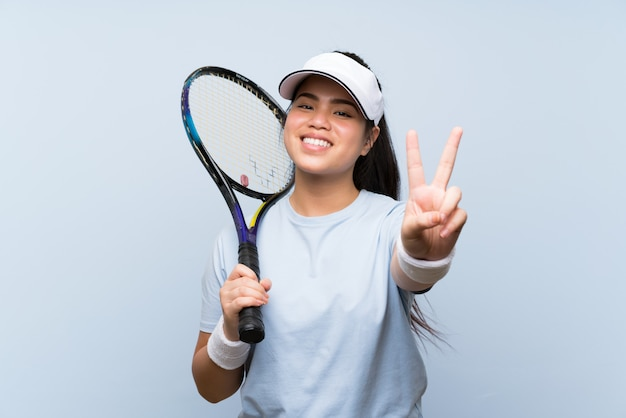 Young teenager asian girl playing tennis smiling and showing victory sign