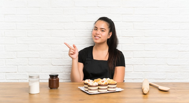 Young teenager asian girl with lots of muffin cake pointing finger to the side