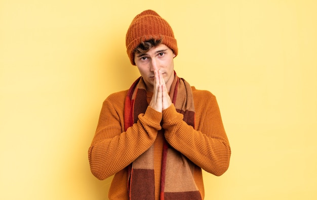 어린 10대 소년은 걱정하고 희망적이며 종교적이며 손바닥을 누르고 용서를 구하며 충실하게 기도합니다.