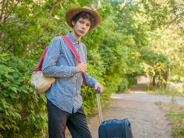 Young teenager boy in summer hat and casual clothes walking with suitcase and put on backpack