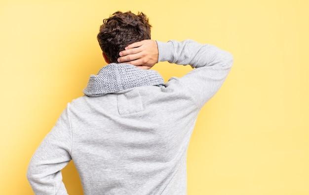 생각하거나 의심하는 어린 10대 소년, 머리를 긁적, 어리둥절하고 혼란스러운 느낌, 뒷모습 또는 뒷모습