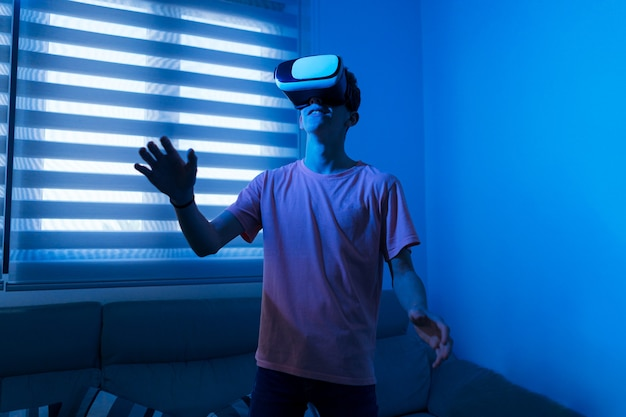 Young teenager boy with virtual reality glasses in his living room