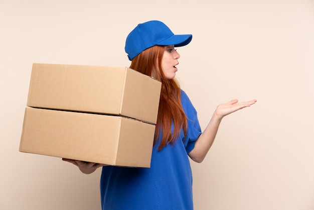Young teenager delivery girl holding copyspace imaginary on the palm