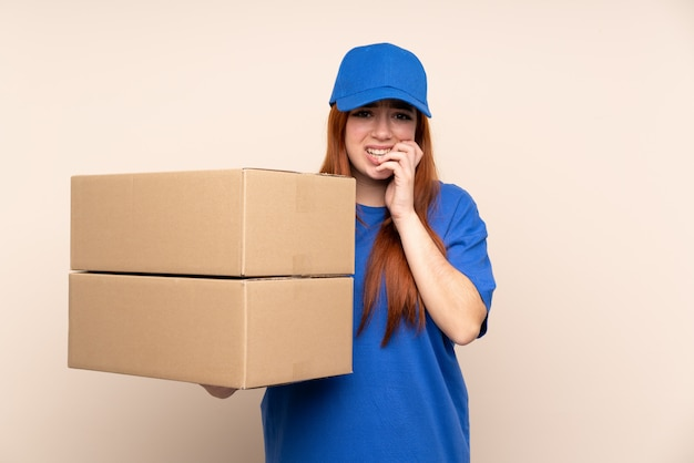 Young teenager delivery girl over isolated wall nervous and scared