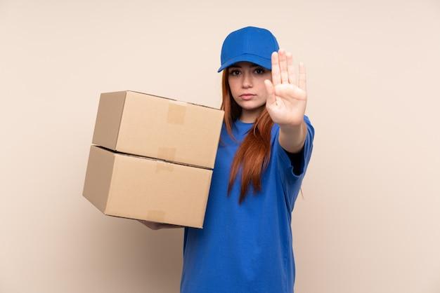 Молодая девушка доставки подростка через изолированную стену, делая остановки жест рукой