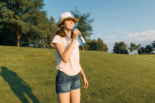 Молодая девушка-подросток пьет освежающую воду из бутылки