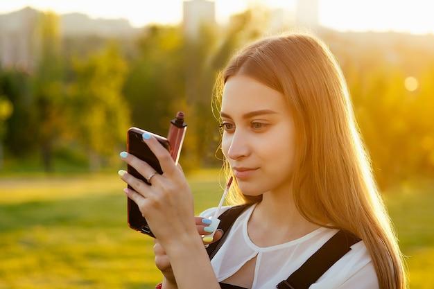 若いティーンエイジャーの女の子の髪の新鮮な肌ときれいな顔は、日没時に公園で電話の反射を見ているメイクアップの口紅を修正します