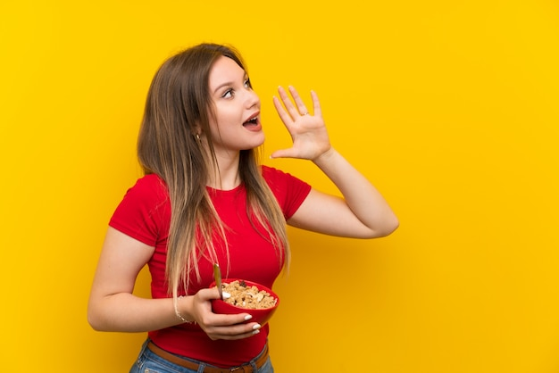Young teenager girl holding a bowl of cereals shouting with mouth wide open