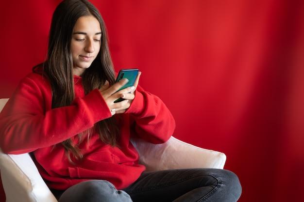 スマートフォンを持っている若い10代の少女。赤いクリスマスの背景にソーシャルコンテンツを見る。