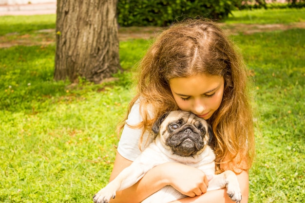 Young teenager girl hugs her pug dog in the park on the green grass
