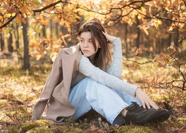 秋の森の若い10代の少女。秋の色。ライフスタイル。秋の気分。森