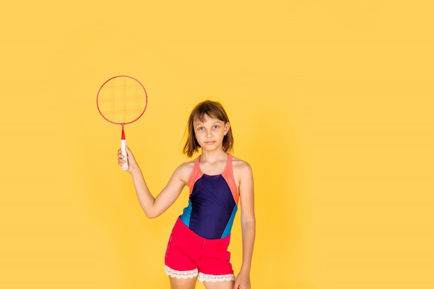 Young teenager girl jumping and playing badminton on yellow wall