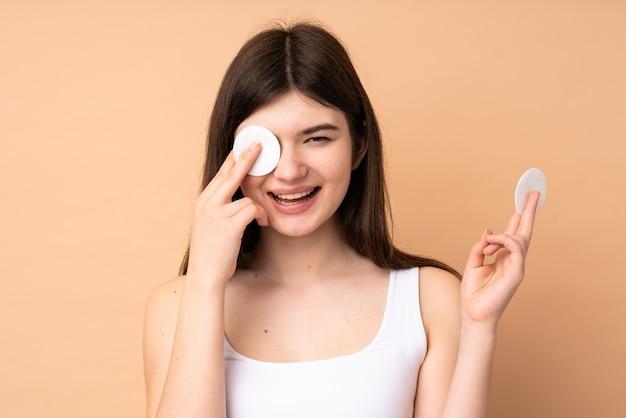 Молодой подросток девушка через стену с ватным тампоном для снятия макияжа с ее лица и улыбки