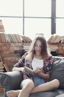 Молодая девушка подростка читая книгу дома