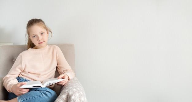 집에서 책을 읽는 젊은 십 대 소녀. 원격 교육, 가정 교육. 자기 격리 개념. 텍스트를위한 공간 복사