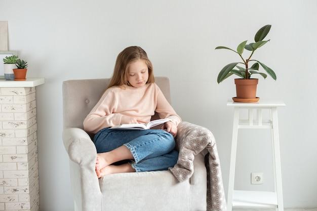 집에서 책을 읽는 젊은 십 대 소녀. 원격 교육, 가정 교육. 자기 격리 개념