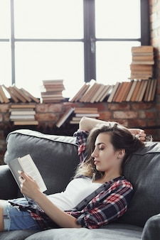 Young teenager girl reading a book at home