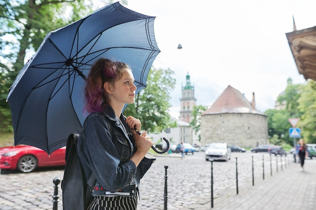 Young teenager girl under an umbrella on the street of city