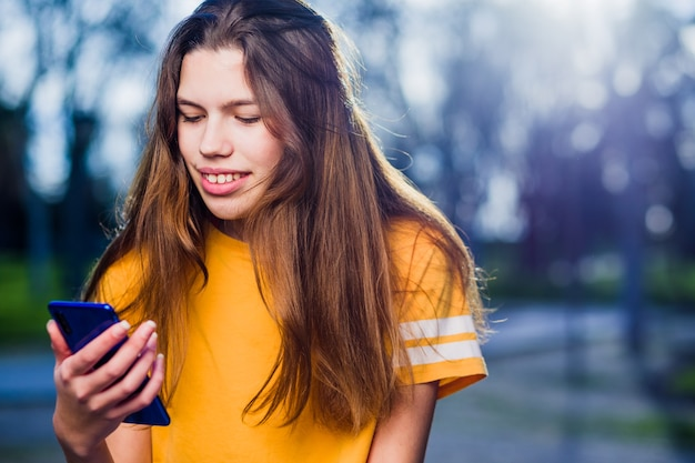 Young teenager girl using a smartphone, lifestyle colorful pretty happy latin female in spain