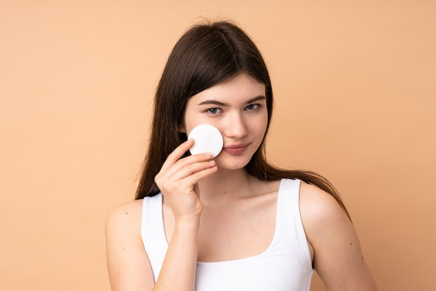 Young  teenager girl over wall with cotton pad for removing makeup from her face