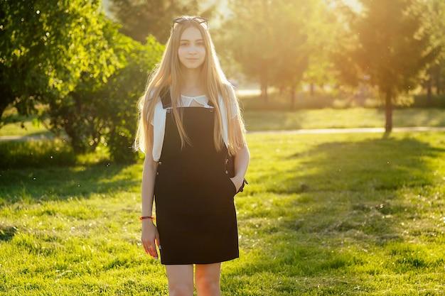 日没時の公園で長いブロンドの髪を持つ若い10代の少女