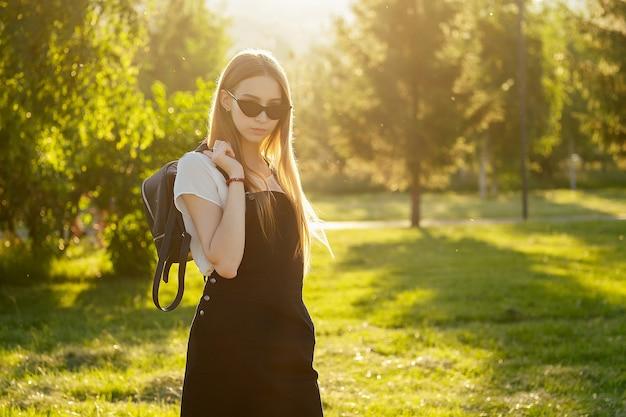 日没時に公園でバックパックと学校の制服の黒いドレスで長いブロンドの髪を持つ若いティーンエイジャーの女の子。
