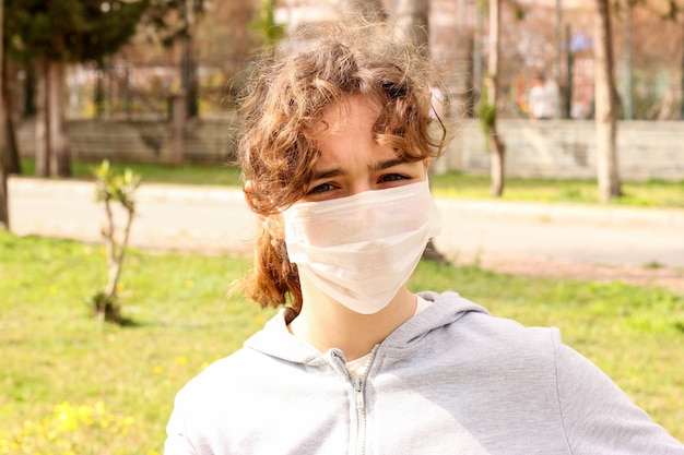 Young teenager girl with a medical mask in a park on a bench. quarantine and isolation during coronavirus